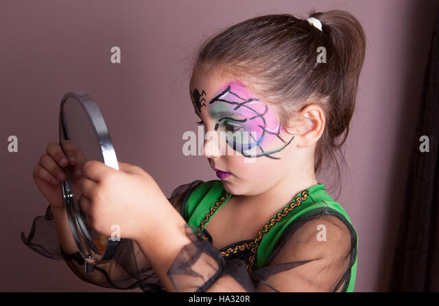 Little girl looking into the mirror after face painting session before halloween party - Stock Image