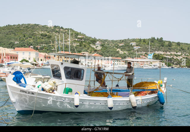 fishermen on fishing boat moored in the port town of Gaios, the capital of the tiny Ionian island of Paxos, Greece - Stock Image
