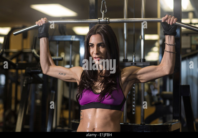 Mid adult woman using bar in gym for pectoral exercise - Stock Image