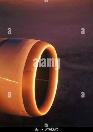 Jet engine in flight reflecting sunrise light - Stock Image