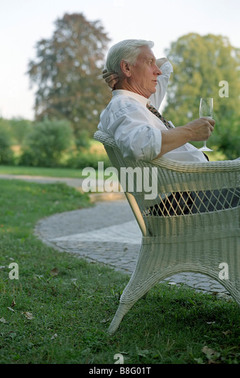 Old Man in a Cane Chair with a Champagne Glass in his Hand - Garden - Festivity - Twilight - Stock Image