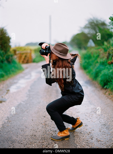 A woman crouching to take a photograph on a country road. - Stock Image