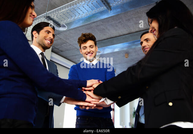Happy co-workers making pile of hands - Stock Image