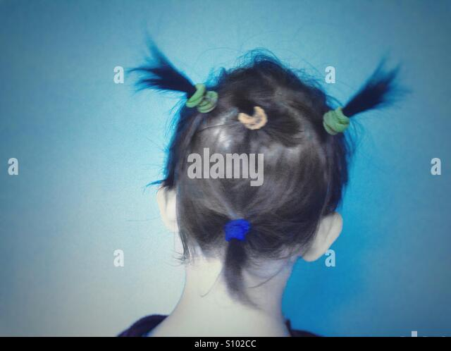Back view of a baby with colorful tires ponytails - Stock Image