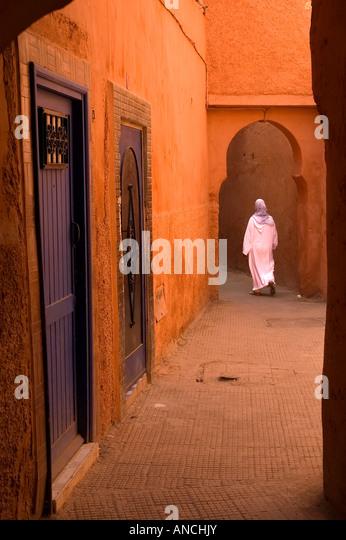 Muslim woman in white jellaba walking in the mysterious red medina of Marrakech - Morocco. - Stock-Bilder