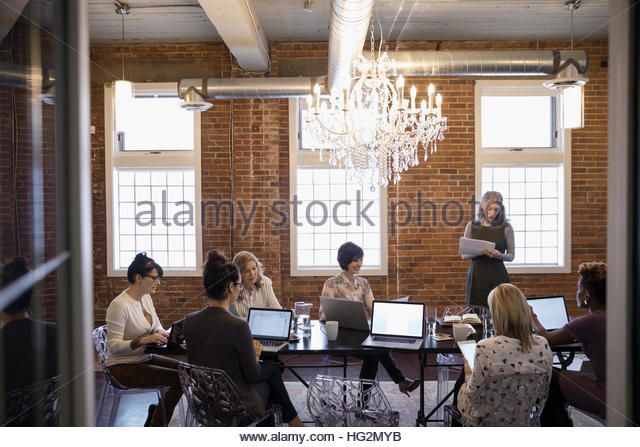 Businesswomen meeting using laptops in conference room - Stock Image