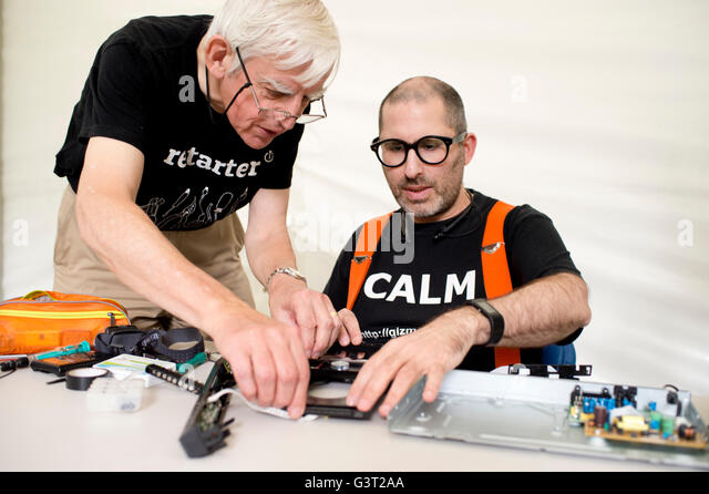 Restart project . A man wearing a t shirt saying 'calm' fixes a broken dvd player,helped by another engineer - Stock Image