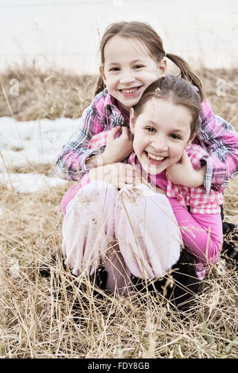 Two smiling sisters hugging in country field - Stock Image
