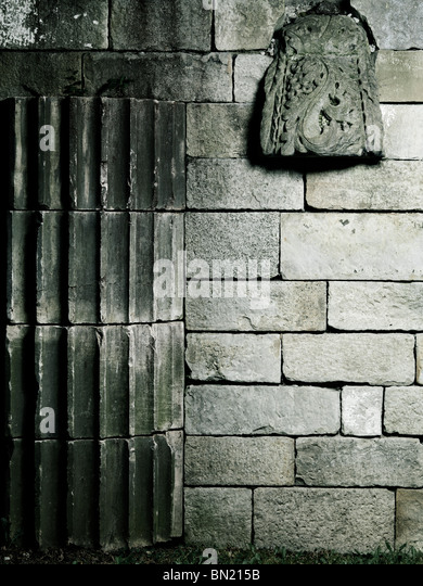 Old stone wall with architectural details artistic background - Stock Image