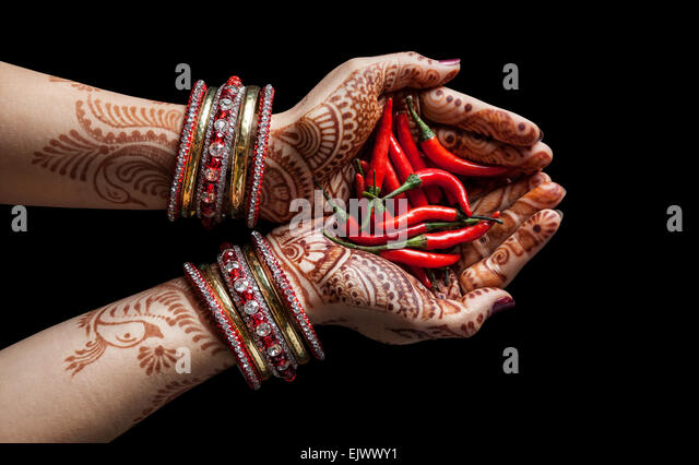 Woman hands with henna holding red chili isolated on black background with clipping path - Stock Image