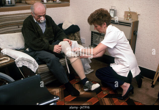 home help carers district nurse on a home visit to elderly man in sheltered accommodation assisting with fitting - Stock Image