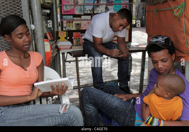 Santo Domingo Dominican Republic Calle Caracas used books book vendor bookseller business stall reading Black man - Stock Image