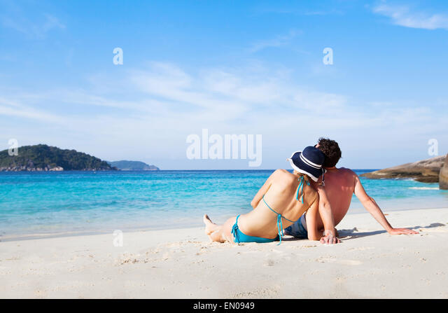 couple sitting and relaxing on the paradise beach during their honeymoon - Stock Image