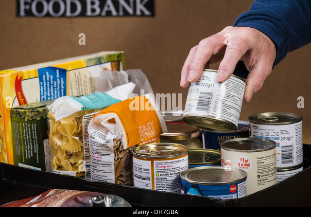 Preparing a food box at a food bank. - Stock Image