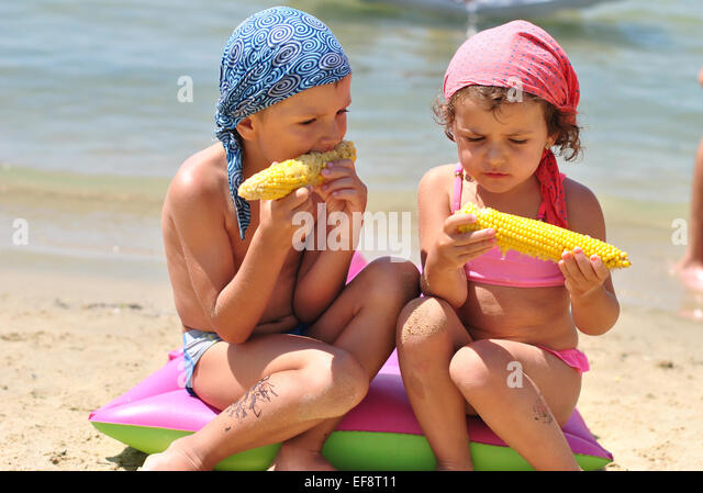 Portrait of girl (2-3) and boy (4-5) eating sweetcorn on beach - Stock Image