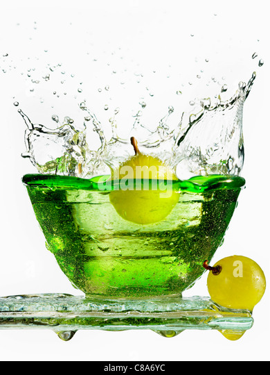 A grape falling into a fresh bowl of water - Stock-Bilder