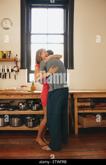 Happy young woman being hugged by her boyfriend in the kitchen. Cheerful young couple embracing each other in morning - Stock Image