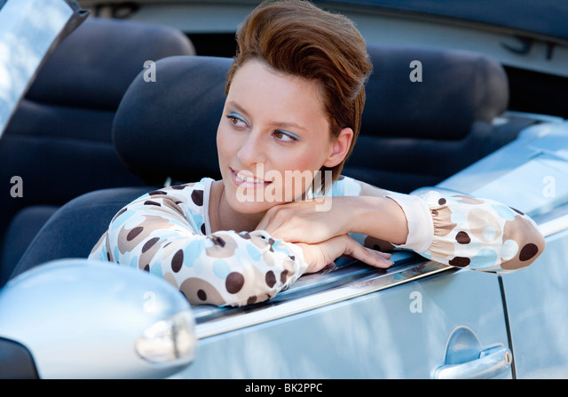 Woman leaning out of car window - Stock Image