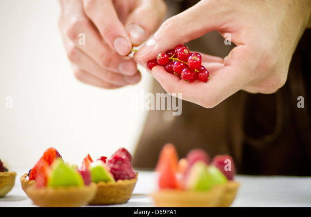 Baker making fruit tarts in kitchen - Stock Image