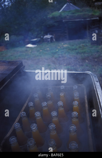 Bramley apple juice bottled up and placed in pasteurisation tanks Tinker s bubble - Stock Image