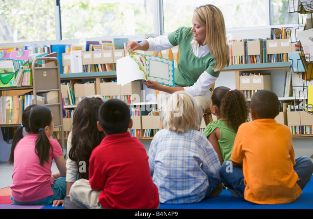 Teacher in class reading to students - Stock Image