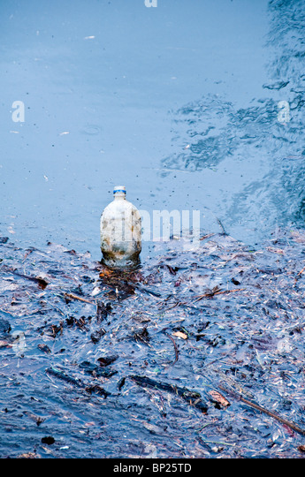 a plastic bottle abandoned into water, pollution concept - Stock Image