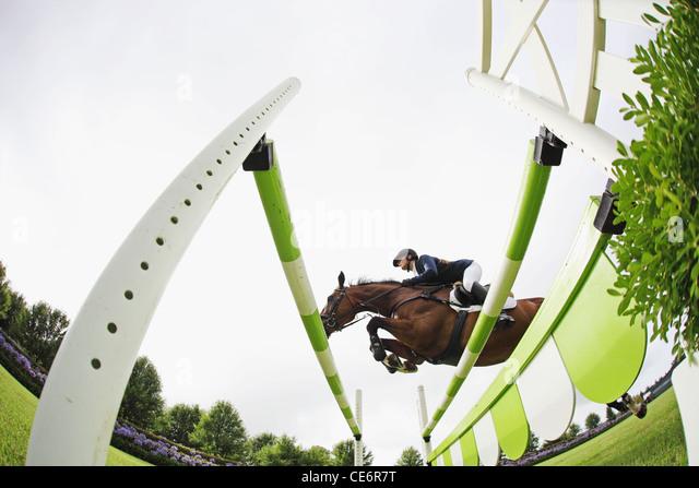 Horseback Rider Jumping Hurdle - Stock Image