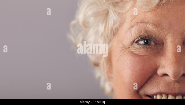 Part of senior woman face with focus on grey eyes. Old woman face close-up with copy space on against grey background. - Stock Image