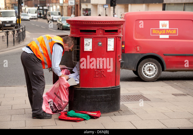 A Royal Mail postman UK emptying mail from a mailbox, with his red Royal Mail van, York, Yorkshire UK - Stock Image