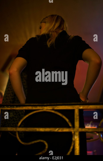 Woman in night club leaning against balcony railing looking away with air of boredom - Stock Image
