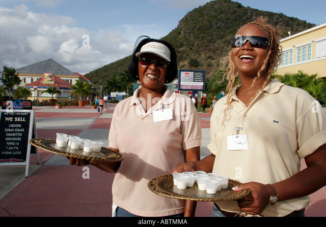 Sint Maarten Philipsburg Dutch Black women greet free drink sample cruise dock entrance Point Blanche Mountain - Stock Image