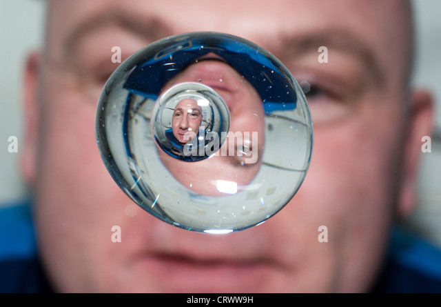European Space Agency astronaut Andre Kuipers watches a water bubble showing his reflected image float freely in - Stock Image
