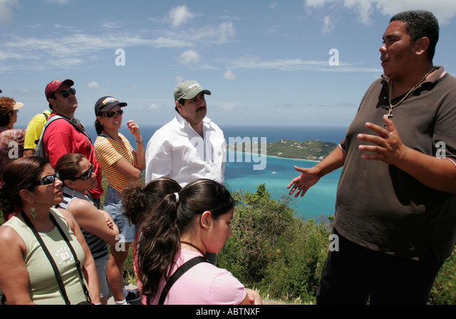 St. Thomas USVI North Side Skyline Drive Megans Bay Overlook Atlantic Ocean Hispanic tour guide - Stock Image