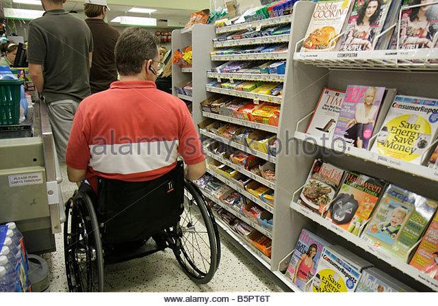 Miami Beach Florida Publix Grocery Store supermarket food checkout line cashier man wheelchair accessibility handicap - Stock Image