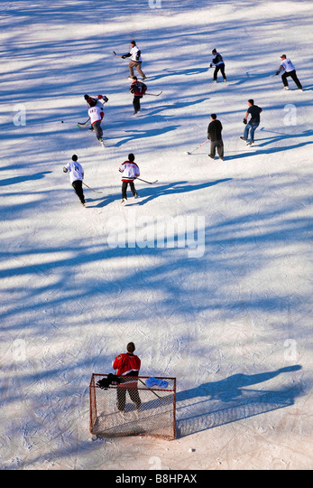 Boys playing, ice hockey game, outdoor rink, high angle view.  Assiniboine River, Winnipeg, Manitoba, Canada. - Stock Image