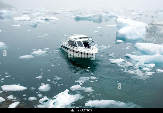 Boat among ice blocks, Sermilik Fjord, East Greenland - Stock Image