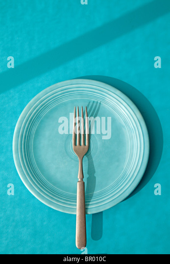 fork on blue fiesta plate - Stock Image
