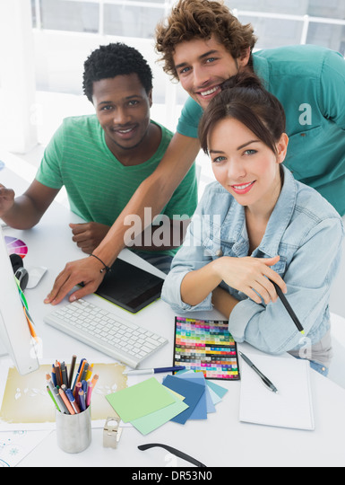 Portrait of three smiling artists at the office - Stock Image
