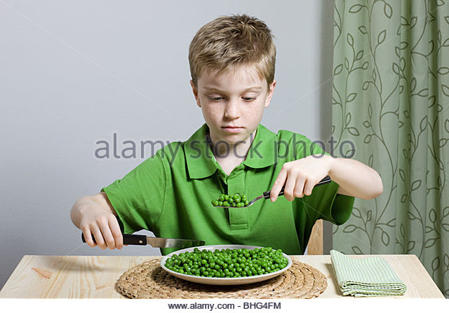 Boy with plate of peas - Stock Image