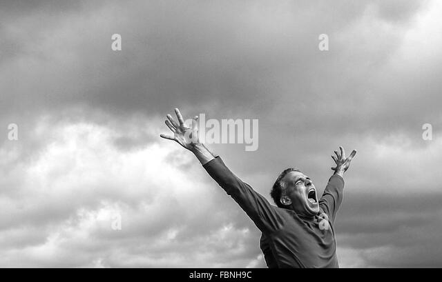 Man Shouting With Arms Raised - Stock Image
