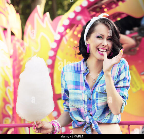 Toothy Smile. Young Woman with Cotton Candy in Amusement Park - Stock Image