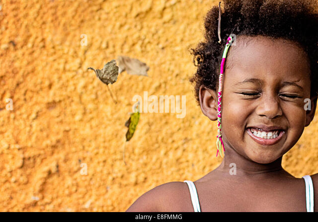 Portrait of a smiling girl standing against yellow wall - Stock Image