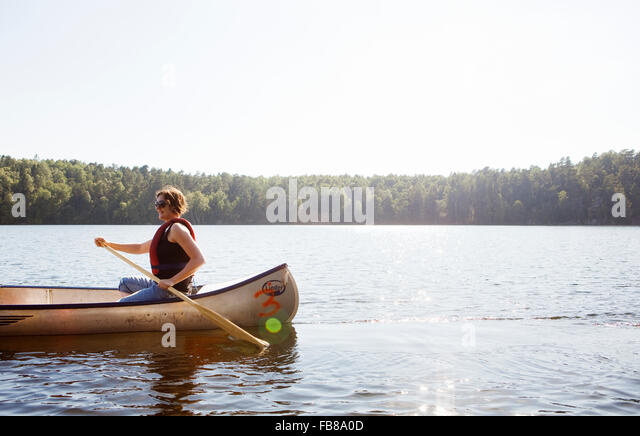 Sweden, Vastra Gotaland, Delsjon, Mid-adult woman in rowboat on lake - Stock Image