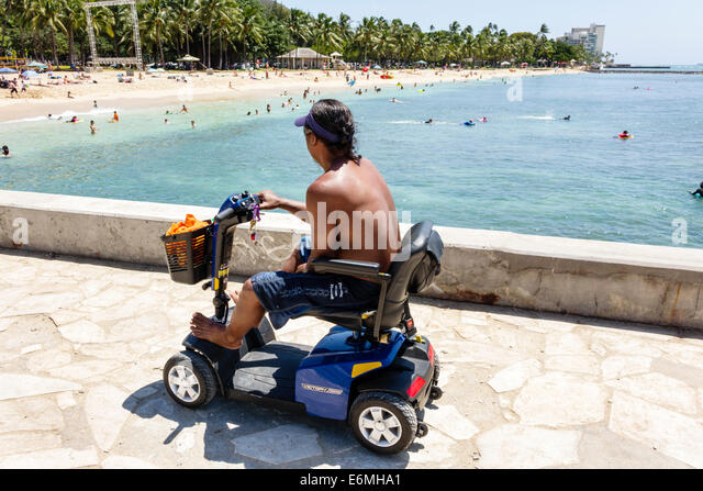 Hawaii Hawaiian Honolulu Waikiki Beach Sans Souci State Recreational Park Pacific Ocean man electric cart transportation - Stock Image