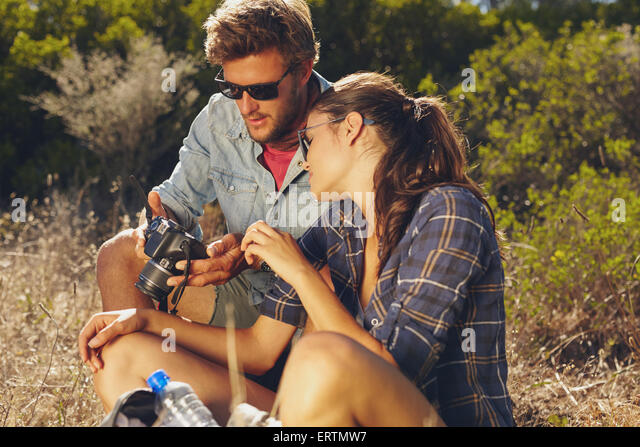 Young couple outdoors together looking at pictures on digital camera. Young man woman on hiking trip taking break. - Stock Image