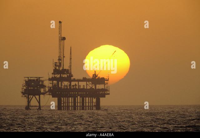 Offshore petroleum drilling rig seen at sunset - Stock-Bilder