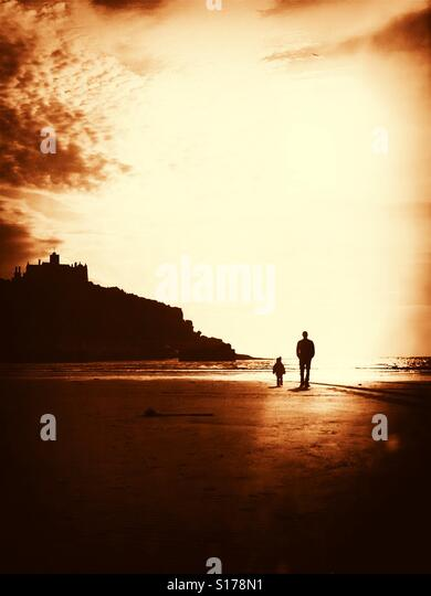 Father and child on beach at low sun. - Stock-Bilder