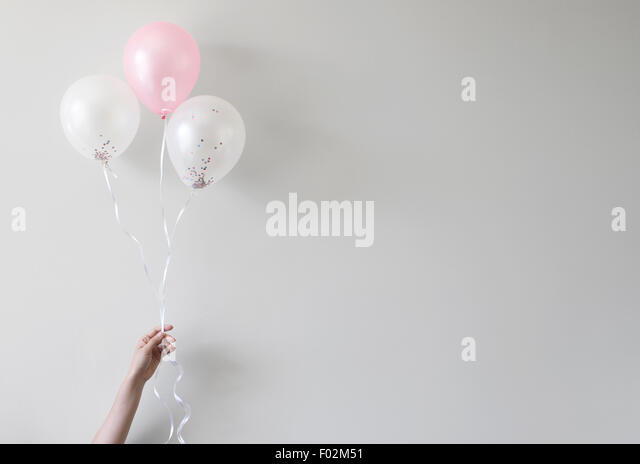 hand holding balloons with confetti inside - Stock Image
