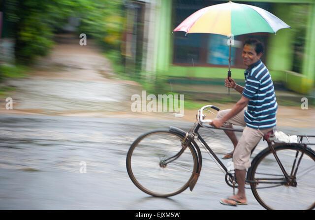 CYCLIST IN SIGIRIYA DURING MONSOON RAIN STORM - Stock Image