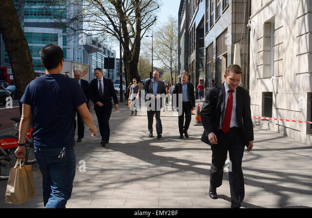 man in jeans & T-shirt walking past men in suits on pavement in London - Stock Image
